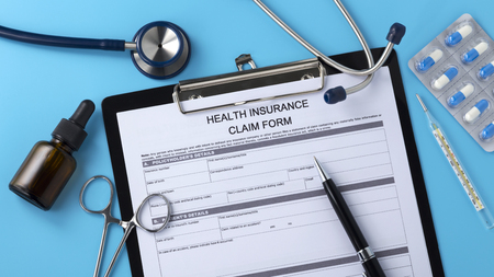 Health insurance claim form with pen on blue background