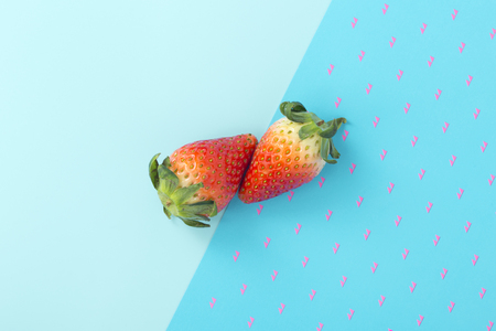 Strawberries on two tone blue background, flat lay