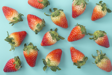 Strawberries on blue background, closeup, flat lay