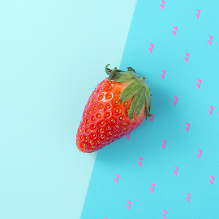 Strawberry on two tone blue background, flat lay