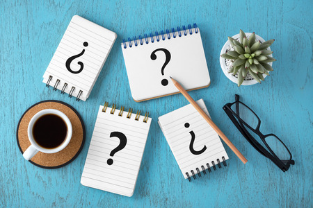 Variety of question marks on notepads with coffee cup on blue wooden desk, top view