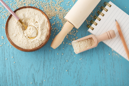 Quinoa flour in bowl with notepad and pencil on blue wooden table, gluten free baking background