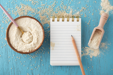 Quinoa flour in bowl with notepad and pencil on blue wooden table, gluten free baking