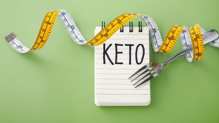 Keto word on notebook with fork and measuring tape on green background, ketogenic concept Фото со стока - 122655071