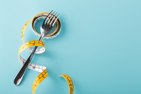 Diet concept on blue background with fork and measuring tape, top view