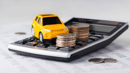 Car and coins on calculator, car loan, buying, leasing Stock Photo
