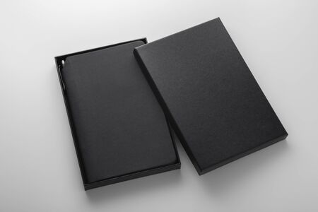 Black notebook, pu leather cover, in box with pen holder, mockup on grey background, business gift Banco de Imagens