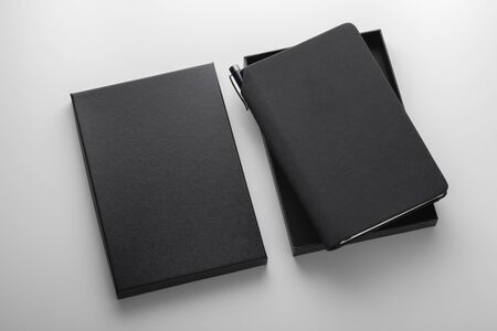 Black pu leather notebook in box with pen holder, mockup on grey background, business gift