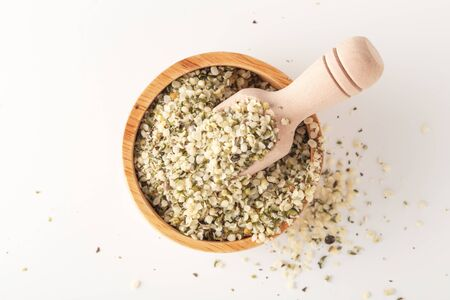 Hemp seeds in wooden bowl with scoop on white background, top view Stockfoto