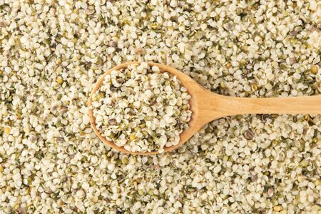Hemp seeds with wooden spoon background, top view Stockfoto
