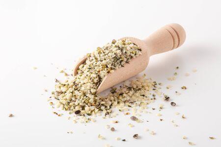 Hemp seeds on wooden scoop on white background Stockfoto