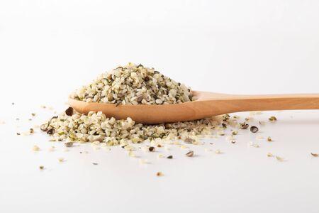 Hemp seeds on wooden spoon on white background Stockfoto