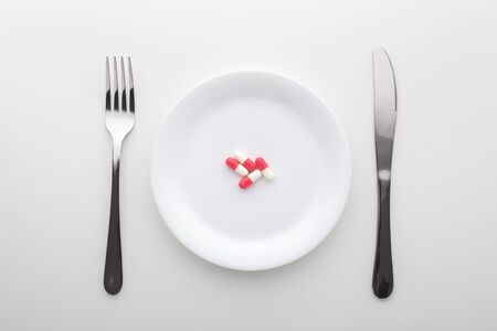 Capsule pills on white plate with fork and knife on white table, top view