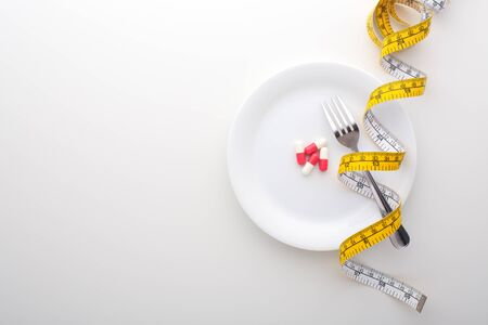 Diet, weight loss background with pills, supplement on plate and measuring tape, top view