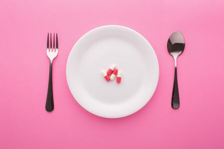 Dietary supplement on plate with fork and spoon on pink background, top view