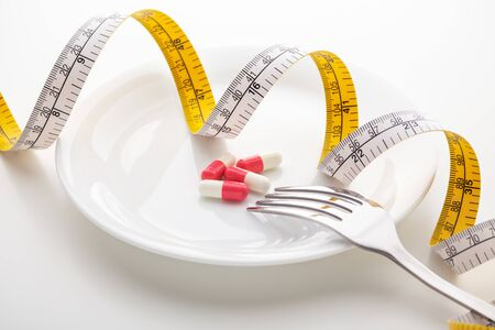 Pills on white plate with fork and measuring tape Stockfoto