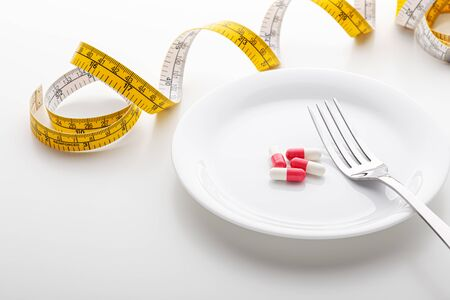 Dietary supplement on plate with fork and measuring tape, diet concept