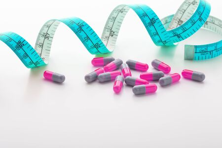 Diet supplements, pills, pink capsule with blue measuring tape on white background 写真素材