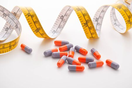 Diet supplements, pills, capsule with measuring tape on white background