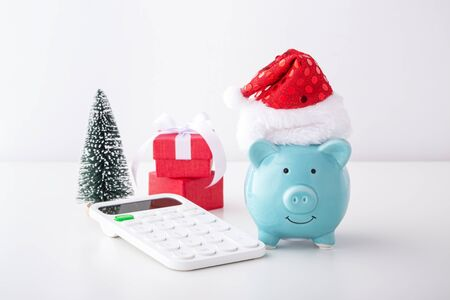Christmas saving concept with piggy bank wearing christmas hat and calculator on white table