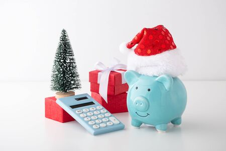 Piggy bank wearing christmas hat with calculator and christmas decor, christmas saving concept