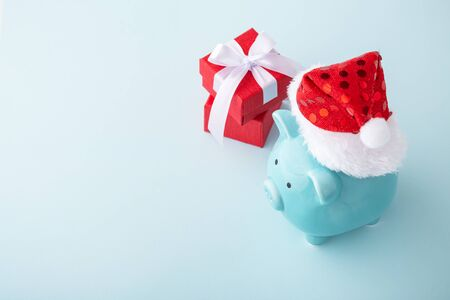 Piggy bank wearing christmas hat with red gift box on pastel blue background, with copy space