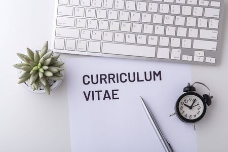 Curriculum vitae with pen and computer keyboard on white table, top view