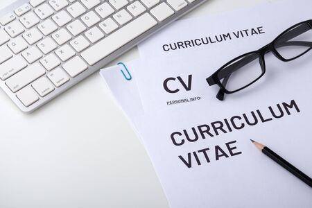 CV with computer keyboard on white desk, job interview