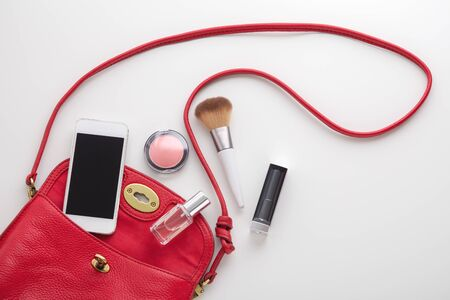 Red woman fashion bag with lipstick, blush, perfume and smartphone on white background, top view