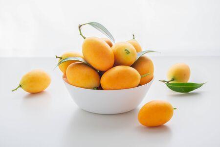 Marian plum or plum mango in white bowl on white table