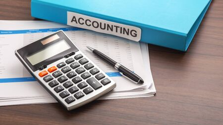 Calculator with accounting report and folder on wooden office desk with copy space. Business accounting and financial concept