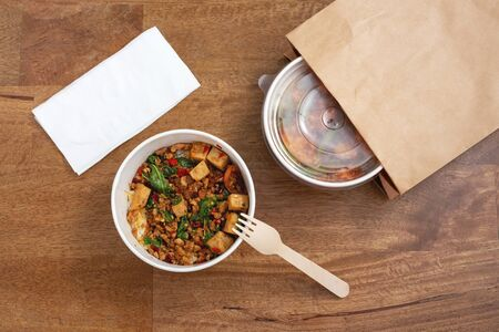 Takeaway asian food delivery. Stir fried pork and basil with rice in paper box on wooden background, top view
