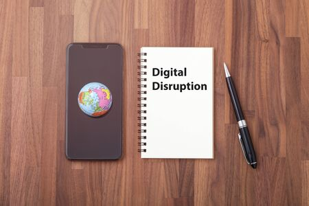 Digital disruption concept with world on smartphone on office desk, top view