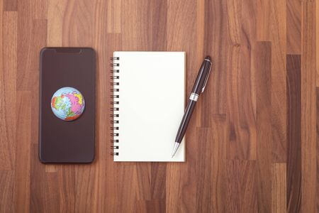 World on smartphone with notebook and pen. Digital business technology concept
