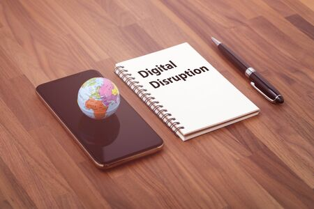 Digital disruption text on notebook with world on smartphone Stock Photo