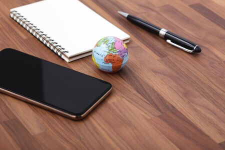 Smart phone with world map and notebook on wooden office desk