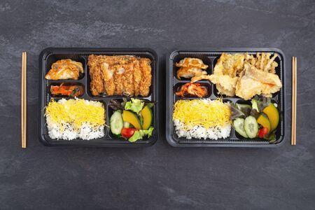 Japanese food bento set in takeaway box on dark stone background