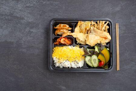 Japanese bento set with salmon and shrimp tempura on dark stone background, flat lay