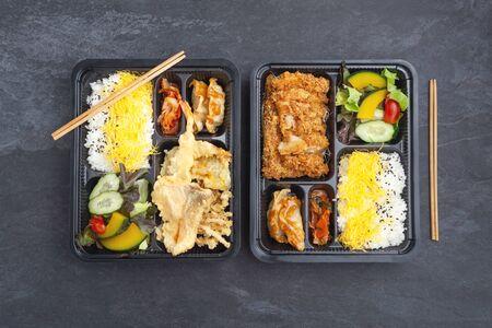 Japanese food bento set in takeaway box on dark stone background, flat lay