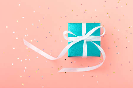 Reward gift box with glitter on pastel pink background