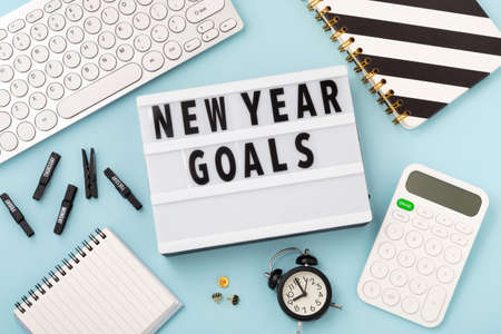 New year goals text on lightbox with office accessories on blue background, flatlay