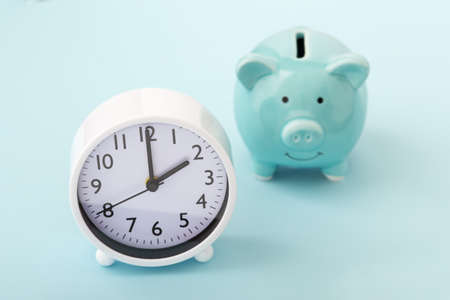 Clock with piggy bank on blue background 版權商用圖片