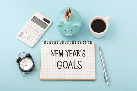Financial goals for new year concept with piggy bank and calculator on blue background