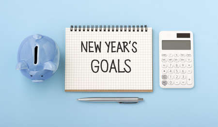 New year goals text on notebook with piggy bank and calculator on blue background