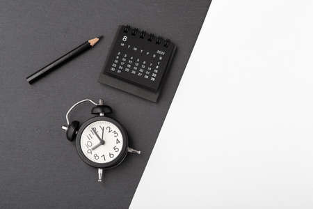Calendar with alarm clock on black and white background, top view, business schedule, event concept Standard-Bild