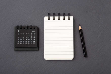 Calendar with notebook on black stone background, top view