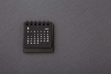 Black calendar on black stone background, closeup, top view