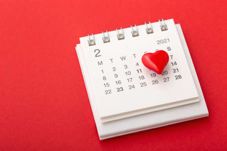 Valentines day concept with calendar and love heart on red background