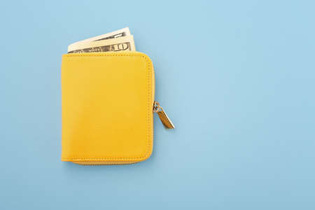 Yellow wallet with cash on blue background, top view with copy space