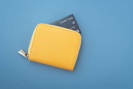 Credit card in yellow wallet on blue background, flatlay, copy space 版權商用圖片